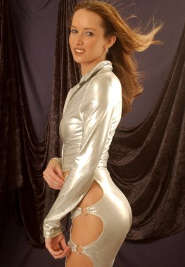 Shiny silver reflective racy disco dancing bodysuit - adorable red haired professional model - black background copy space - party lady in party mood - tone butt cheeks backside rear end behind view of curved buttocks