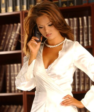 White satin robe and pearl necklace on sexy sultry brunette on making a phone call from indoor library