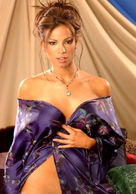 Dark blue flowered satin robe on sexy alluring brunette kneeling in bed indoor bedroom setting tan background healthy attitude of a carefree babe in golden light adorable fun alluring look natural look of a real beauty sexual sensual goddess