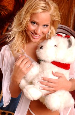 Scruffy white teddy bear gets hugs from pretty blonde girl smiling enchanting bewitching lovely lady captivating engaging endearing eyes delightful body fun alluring look naughty college school girl pinup poster perfect for calendar