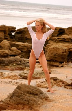 Lauren Thompson wearing one piece sheer white thong swimsuit on beautiful long haired blonde posing on the beach on rocks sand ocean beach on tropical island  sleek slim hour glass shape natural perky suggestive provocative beauty naughty college