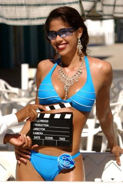 Clapboard in front of skimpy blue string bikini hot smiling enchanting bewitching lovely lady captivating engaging endearing eyes standing sleek slim hour glass shape natural perky suggestive provocative beauty naughty college school girl pinup