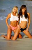 Bílé střižené trička na sůl a pepř sestra model - blondýny a brunetky nejlepší přátelé pózují v mělkém oceánu moře písek vody na tropickém ostrově pláž klečí elegantní štíhlé hodiny sklo tvar přírodní energické sugestivní provokativní krásy ohromující