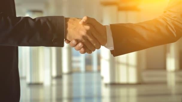 Ti dva obchodníci si potřásli rukou na slunném pozadí. zpomalený pohyb