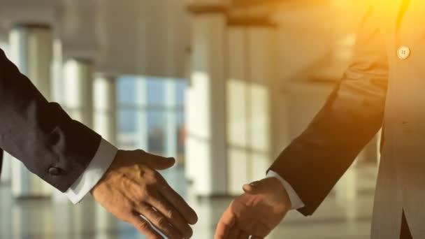 Dva obchodníci si potřásli rukou na slunném pozadí. zpomalený pohyb