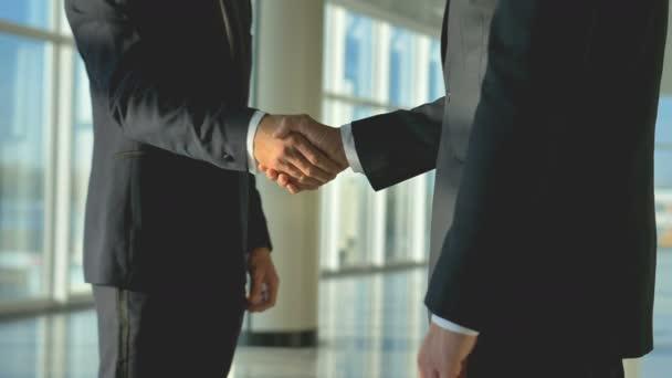 Ti dva obchodníci si potřásli rukou v kanceláři. zpomalený pohyb