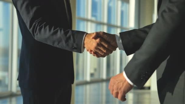 Dva byznysmeni si potřásli rukou v kanceláři. zpomalený pohyb