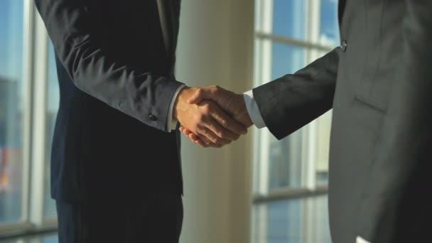 Ti dva muži si potřásli rukou v kanceláři. zpomalený pohyb
