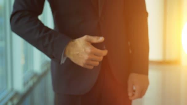 Obchodník, který dává otevřenou ruku na slunném pozadí. zpomalený pohyb