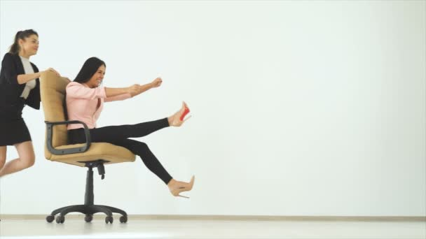The two happy businesswomen playing with a chair. slow motion