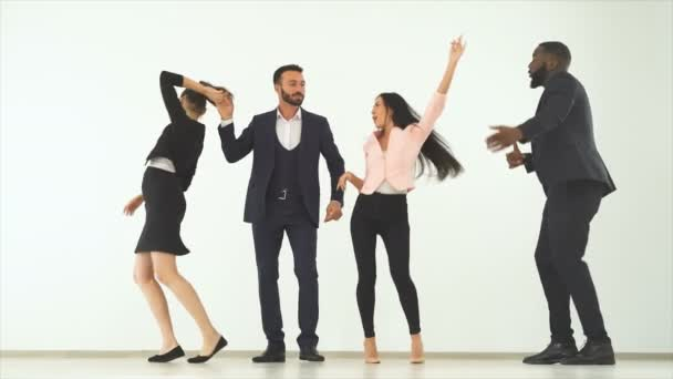 The four happy people dancing on the white background. slow motion
