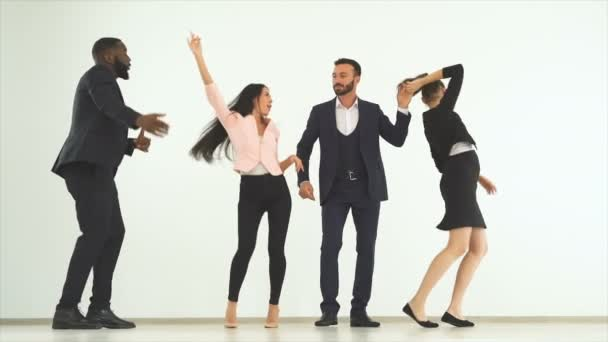 The four business people dancing on the white background. slow motion
