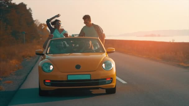 The young people have fun traveling by cabriolet. slow motion