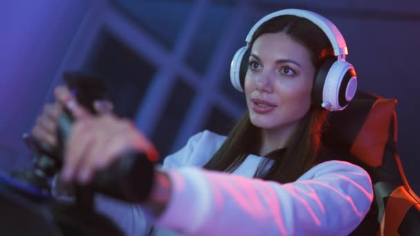 The attractive gamer girl with headphones plays video games