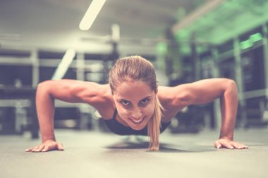 The happy sportswoman doing push up exercise in the gym