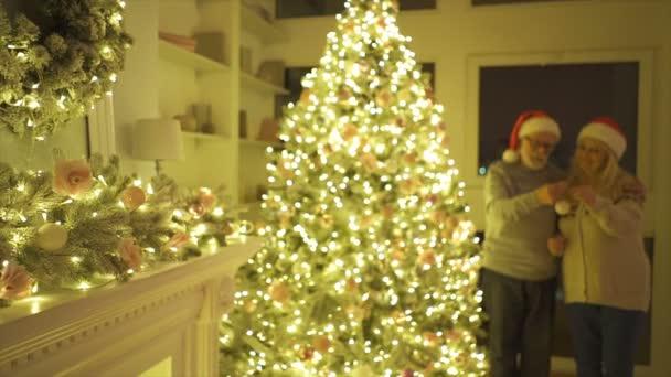 Starý muž a žena zdobí vánoční stromek. zpomalený pohyb