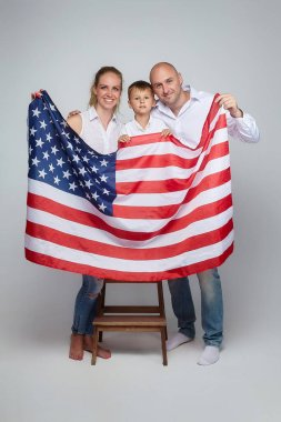 happy family of three poses with an American flag. photo session in the Studio