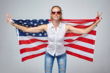 blonde girl. posing with usa flag in studio on white background