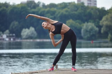 Attractive girl in sportswear does gymnastic exercises on a wooden pier in a city park.
