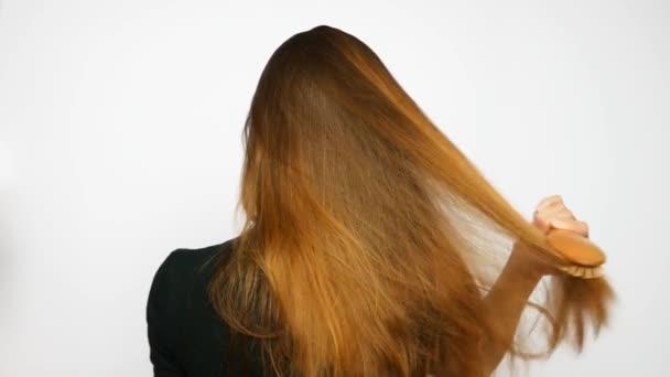 Mladá krásná žena česá své dlouhé luxusní vlasy