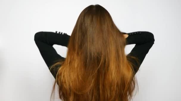 Egy fiatal, gyönyörű nő kiegyenesíti fényűző haját.