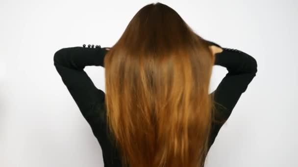Egy fiatal, gyönyörű nő kiegyenesíti hosszú, fényűző haját.