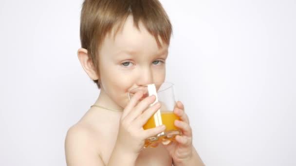 Egy gyönyörű meztelen fiú friss narancslevet iszik egy pohárból.