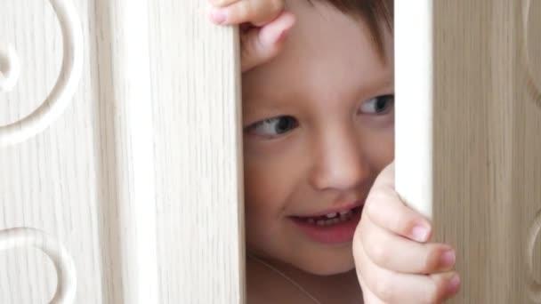 Egy kis aranyos fiú jól érzi magát egy fehér szekrényben.