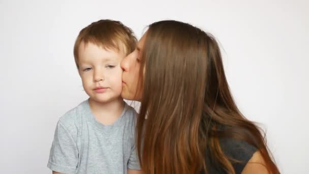 A young beautiful mom kissing her pretty son on the cheek against white background