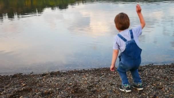 Ein kleiner Junge in Jeans-Overalls wirft Steine ins Wasser, während er am Flussufer steht