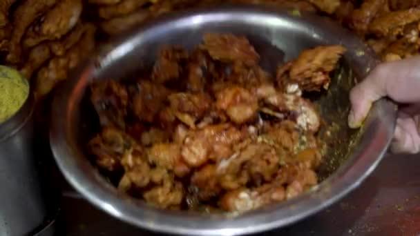 Sült csirke fűszerezése sóval és keverés acéltálba.