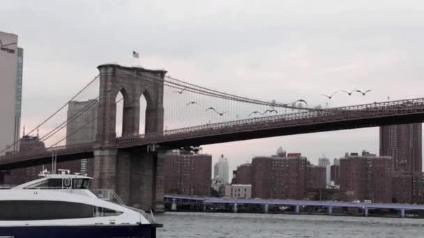 Jachta nebo loď plující přes řeku před panorama New Yorku.