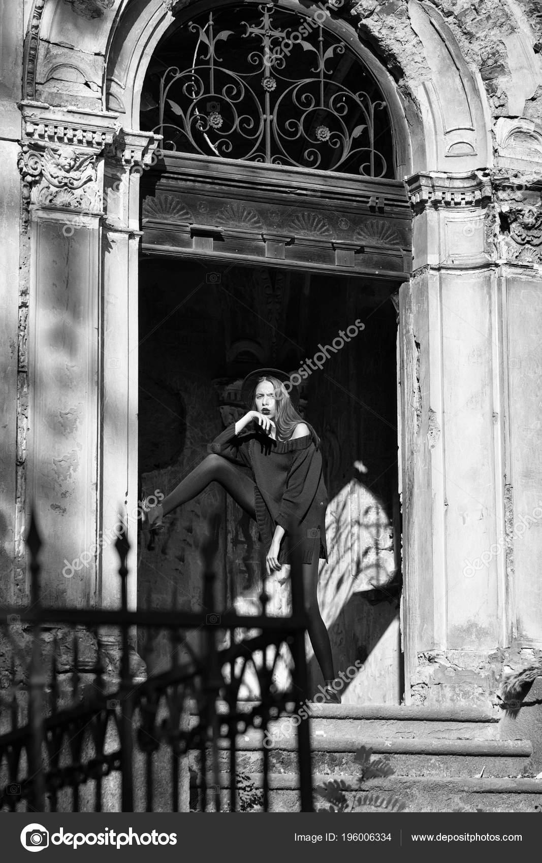 0f707d12d5b5b Moda mujer o chica con labios rojos en cara bonita en vestido posando junto  a la puerta de hierro de la vieja y sombrero negro arruinado edificio  escaleras ...