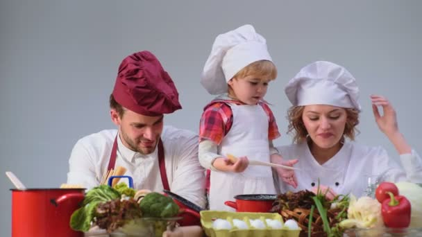 Der süße kleine Junge und seine schönen Eltern lächeln beim Kochen in der Küche. junge Familie kocht Essen in der Küche. glückliche Familie Kochen zusammen. glückliche junge Familie mit Mama, Papa und Kind beim Kochen
