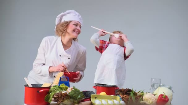Cute little boy and his beautiful mother smiling while cooking in kitchen. Young family cooking food in kitchen. Young mother and son cooking meal together.