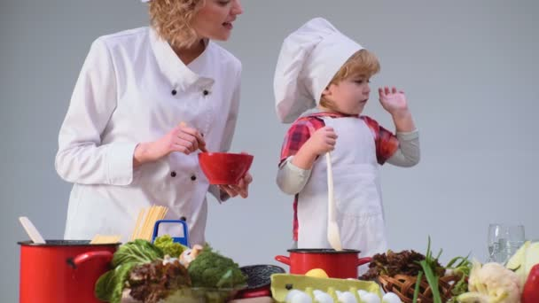 Cute little boy and his beautiful mother smiling while cooking in kitchen. Young family cooking food in kitchen. Young mother and son cooking meal together
