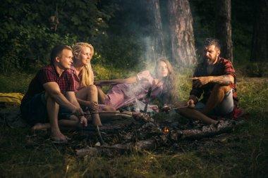Ormanda kamp arkadaş grubu. İki Çift sopa üzerinde Sosis kızartma. Kamp ateşi etrafında konuşmak gençler.
