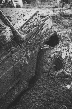 Fragment of car stuck in dirt, close up.