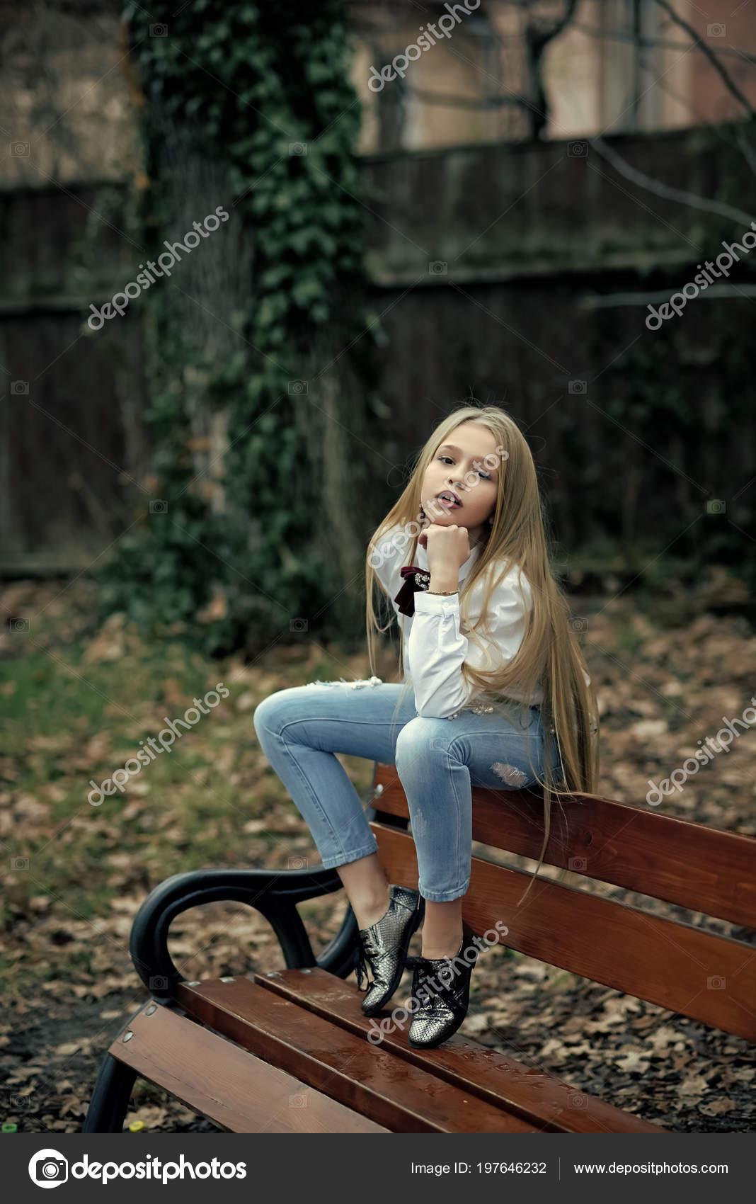 Mädchen In Modische Jeans Sitzen Auf Bank Mode Kleines Kind Mit