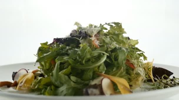 Salát podáváme v bílé plotně, tmavé dřevěné pozadí. Restaurace jídlo koncept. Jídlo v restauraci.