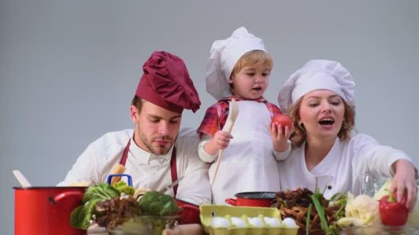 Děti enyoj hezký den. Roztomilý malý chlapec a jeho krásné rodiče se usmívají při vaření v kuchyni. Mladá rodina vaření v kuchyni. Šťastná rodina, společné vaření. Mladá rodina s maminkou