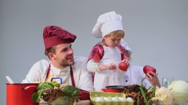 Dětství. Roztomilý malý chlapec a jeho krásné rodiče se usmívají při vaření v kuchyni. Mladá rodina vaření v kuchyni. Šťastná rodina, společné vaření. Mladá rodina s mámou, táta dítě