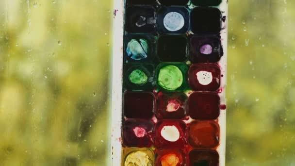 Akvarel se maluje. Kapky vody na okně s zelená záře