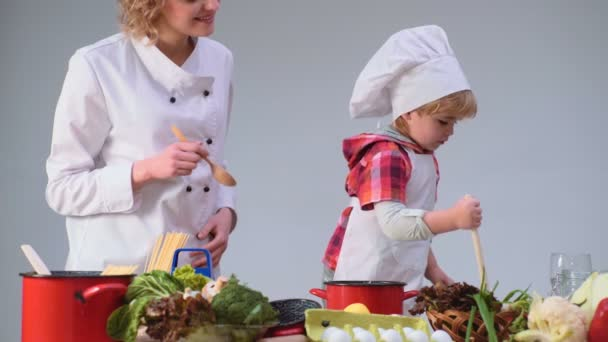 Kid play  Cute little boy and his beautiful parents are smiling while  cooking in kitchen  Young family cooking food in kitchen  Happy family  cooking together  Happy young family with Mum, Dad child