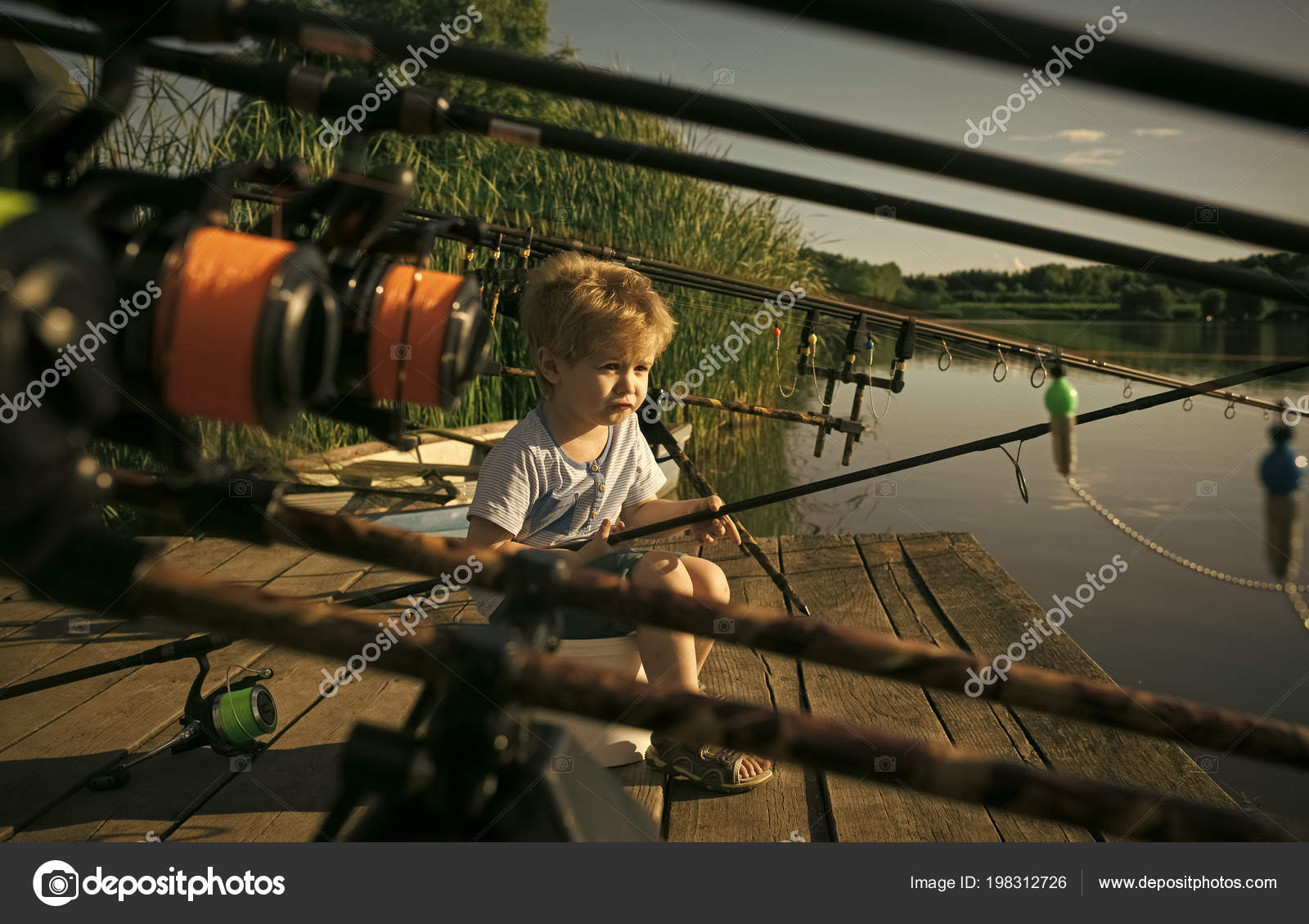 a1e41d9ed1fc9 Kid play. Little baby boy fishing on bank of river with fishing rod ...