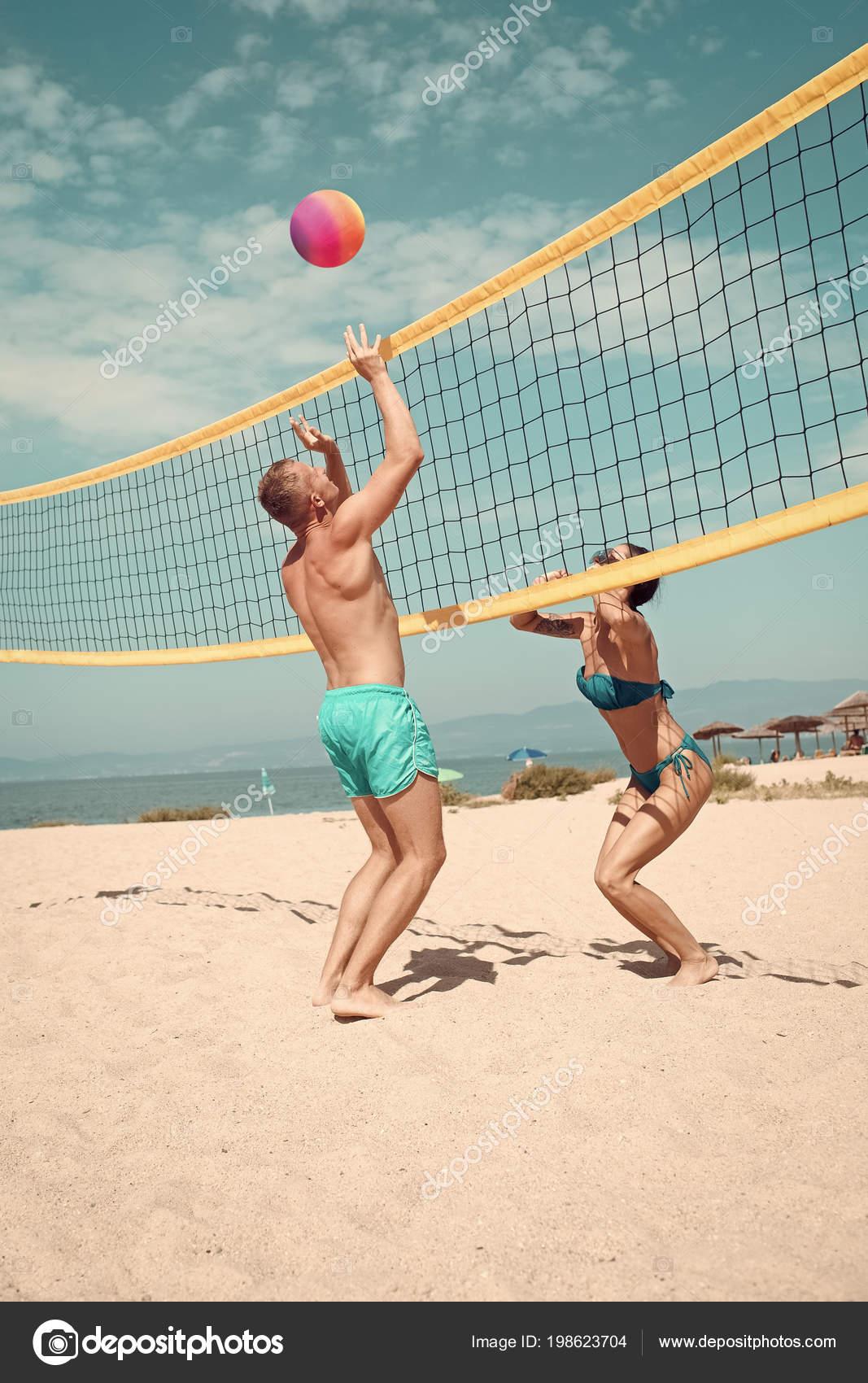 44aed15778d08 Concepto de voleibol de playa. Par divertirse jugando voleibol. Joven  pareja activo deportivo bata de voleibol