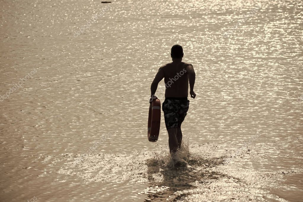 beach lifeguard. Man back silhouette with red life ring