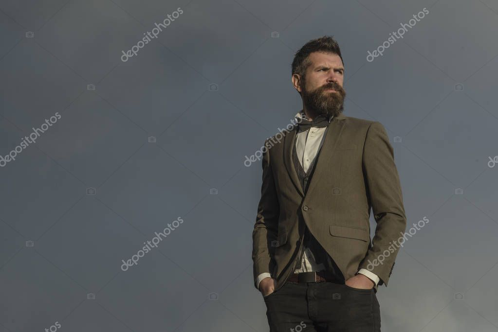 Hipster with beard and mustache on unshaven face. Bearded man on cloudy sky. Fashion businessman wear classic coat with bow tie. Freedom and success. Vacation travelling and wanderlust, copy space