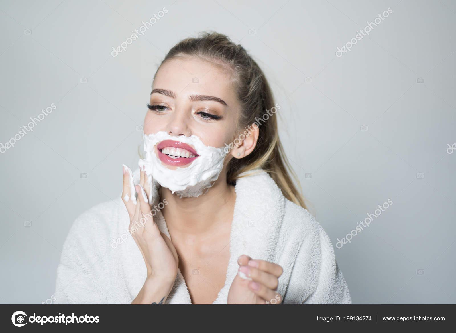 3b1c7350d98cee Mädchen auf lächelndes Gesicht im Bademantel für Gesicht mit Schaum  rasieren, grauen Hintergrund. Hautpflege und Rasieren Konzept. Frau mit  Gesicht bedeckt ...