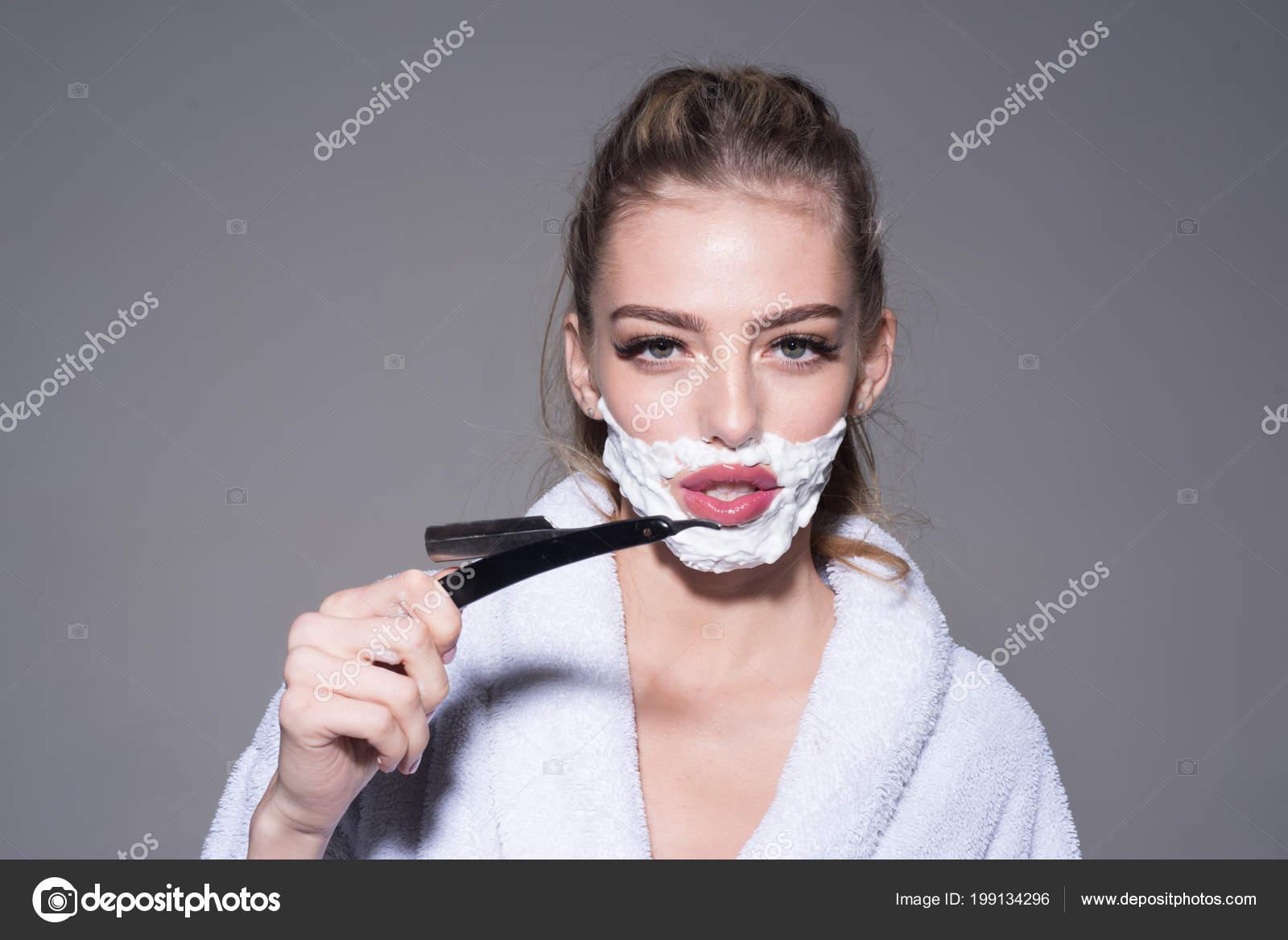 73c7f8bccf36b8 Blonde Frau mit frechen Look tragen weiße Bademantel auf grauem Hintergrund  isoliert. Morgen rasieren, junge Frau mit Schaum auf ihrem Gesicht Holding  ...